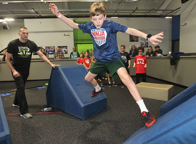 Candace H. Johnson-For Shaw Media Pro Ninja Brandon Mears, of St. Charles watches Jason Cameron, 10, of Northbrook get through the quintuple steps obstacle course during Pro-Camp V at Ultimate Ninjas in Libertyville. (1/5/19)
