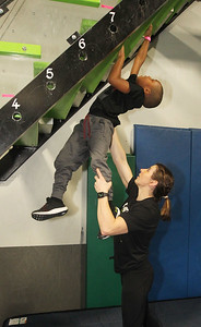 Candace H. Johnson-For Shaw Media Cole Epps, 6, of Grayslake gets some help from Pro Ninja Barclay Stockett as he uses his arms to climb up the Devil Steps obstacle course during Pro-Camp V at Ultimate Ninjas in Libertyville. (1/5/19)