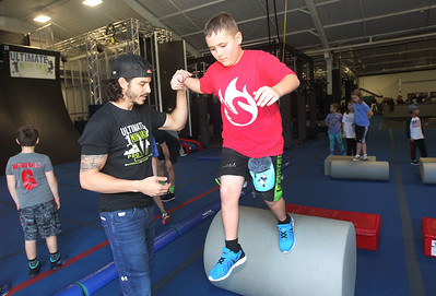 Candace H. Johnson-For Shaw Media Pro Ninja Flip Rodriguez helps Jacob Peterson, 10, of Verona, Wis., conquer the Warrior Rolling Log during Pro-Camp V at Ultimate Ninjas in Libertyville. (1/5/19)