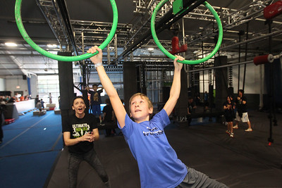 Candace H. Johnson-For Shaw Media Pro Ninja Tori Clement, of Naperville cheers on Chase McDowell, 10, of Long Grove while moving as he holds on to the ring slider during Pro-Camp V at Ultimate Ninjas in Libertyville. (1/5/19)