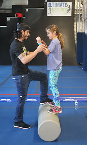 Candace H. Johnson-For Shaw Media Pro Ninja Flip Rodriguez helps Gemma Marinello, 9, of Northfield on the Warrior Rolling Log during Pro-Camp V at Ultimate Ninjas in Libertyville. (1/5/19)