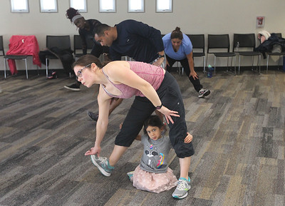 Candace H. Johnson-For Shaw Media Michelle Kora, of Buffalo Grove stretches with her daughter, Kaitlyn, 3, by her side during Zumba for Families at the Wauconda Area Library. The program runs January through February every Saturday from 9:30-10:30 am. (1/5/19)