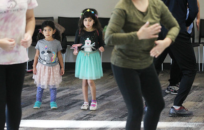 Candace H. Johnson-For Shaw Media Kaitlyn Kora, 3, of Buffalo Grove and her sister, Audrey, 5, watch others keep up as they exercise during Zumba for Families at the Wauconda Area Library. The sisters were at the event with their parents, Vijay and Michelle. The program runs January through February every Saturday from 9:30-10:30 am. (1/5/19)