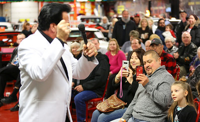 Elvis imperonator performs in front of Elvis's custom-made Cadillac