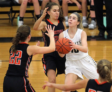 Candace H. Johnson-For Shaw Media Grayslake North's Meghan Leahy drives to the basket against Libertyville's Brooke Bair (#22), Elise Rodriquez and Morgan Spaulding in the fourth quarter at Grayslake North High School. Libertyville won 62-41. (1/12/19)