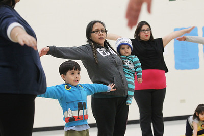 Candace H. Johnson-For Shaw Media Jumberto Bustamante, 4, of Round Lake stretches out his arms while he stands next to his mother, Margarita Franco-Mendez, holding his sister, Kimberly, 1, and Maricela Solis, of Round Lake Beach as they take a Yoga Class sponsored by Mano a Mano at the W.J. Murphy Elementary School in Round Lake Park. (1/11/19)