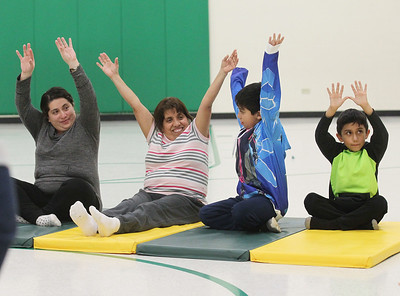 Candace H. Johnson-For Shaw Media Claudia Espinosa, of Round Lake, her mother, Victoria Solorzano, of Round Lake Beach, and her children Francisco, 8, and Giovani, 6, take a Yoga Class sponsored by Mano a Mano at the W.J. Murphy Elementary School in Round Lake Park. Families were encouraged to participate in the class. (1/11/19)