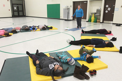 Candace H. Johnson-For Shaw Media Heidi Droessler, of Grayslake, yoga instructor, leads her Yoga Class, sponsored by Mano a Mano, as she works with parents and their children on a final resting pose at the W.J. Murphy Elementary School in Round Lake Park. (1/11/19)