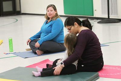 Candace H. Johnson-For Shaw Media Heidi Droessler, of Grayslake, instructor, looks at Ana Martinez, of Round Lake and her daughter, Brooklynn, 2, as she talks to parents and their children about how to do yoga during the Yoga Class, sponsored by Mano a Mano, at the W.J. Murphy Elementary School in Round Lake Park. (1/11/19)