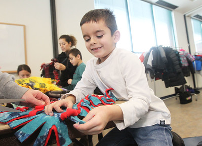 Candace H. Johnson-For Shaw Media Enzo Ivanov, 7, of Round Lake is all smiles as he makes a blanket for a shelter animal at Save-A-Pet during Kindness Crafts-MLK Day ON, Not a Day Off at the Grayslake Area Public Library. Enzo was making blankets at the event with his brothers, Andrei and Viktor, and mother, Stephanie Stefanov. (1/21/19)
