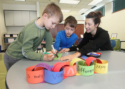 Candace H. Johnson-For Shaw Media Gio Dow, 5, of Grayslake and his brother, Vinny, 7, work with their mother, Rosie, on adding to the symbolic paper chain as they write kind thoughts on paper during Kindness Crafts-MLK Day ON, Not a Day Off at the Grayslake Area Public Library. (1/21/19)