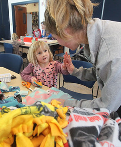 Candace H. Johnson-For Shaw Media Sloane Sprague, 5, gets a high-five from Lilia Begin, 17, a volunteer, both of Grayslake as they work together to make blankets for shelter pets at Save-A-Pet during Kindness Crafts-MLK Day ON, Not a Day Off at the Grayslake Area Public Library. (1/21/19)
