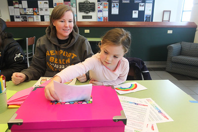 Candace H. Johnson-For Shaw Media Sara Donisch, of Grayslake watches her daughter, Tess, 6, put her handmade get well card into a box for a child who is hospitalized during Kindness Crafts-MLK Day ON, Not a Day Off at the Grayslake Area Public Library. Sara's son, Reid, 9, was also at the library helping to make cards. The get well cards will go to an organization called, Cards for Hospitalized Kids.(1/21/19)
