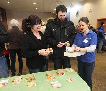 Candace H. Johnson-For Shaw Media Coordinator Carolina Schottland, of Round Lake (on right) shows her mother, Monica Yeko, and brother, Brent, both of Battle Creek, Mich., some seeds to take home for their garden during the 3rd Annual Round Lake Area Garden Club Seed Expo at the Round Lake Beach Cultural & Civic Center. (1/26/19)