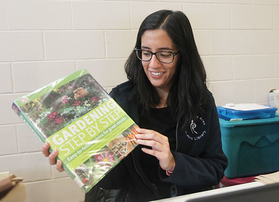 Candace H. Johnson-For Shaw Media Jennifer Puga, of Round Lake, circulation clerk for the Round Lake Area Public Library, shows one of the gardening books that could be taken out from the library during the 3rd Annual Round Lake Area Garden Club Seed Expo at the Round Lake Beach Cultural & Civic Center. The Round Lake Area Public Library co-hosted the seed expo.(1/26/19)