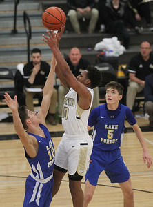 Candace H. Johnson-For Shaw Media Grayslake North's Jamon Thomas is pressured near the basket by Lake Forest's Leo Scheidler and Asa Thomas in the third quarter at Grayslake North High School. Lake Forest won 56-43. (1/7/19)