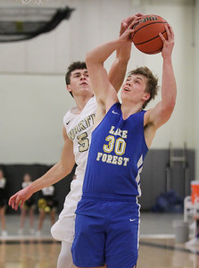 Candace H. Johnson-For Shaw Media Grayslake North's Joe Swanson tries to block a shot by Lake Forest's William Thomas in the fourth quarter at Grayslake North High School. Lake Forest won 56-43. (1/7/19)