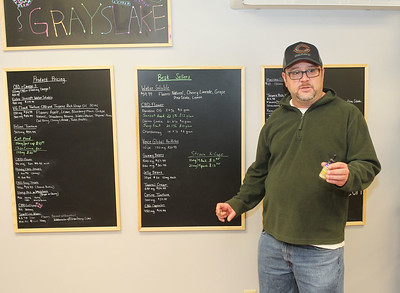 Candace H. Johnson-For Shaw Media Zac Camp, owner, stands in front of his menu boards as he talks about the CBD American Shaman water solubles he sells at CBD Grayslake on Center Street in Grayslake. (1/4/20)