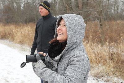 Candace H. Johnson-For Shaw Media Lisa Knight, of Wauconda looks up to see birds in the sky as she holds her monoculars during Walk with a Naturalist at Grant Woods on West Monaville Rd. in Ingleside. Bob Manfredini, of Libertyville stood close by. (1/4/20) The next Walk with a Naturalist will be at the Greenbelt Forest Preserve in North Chicago on Saturday, February 1st, from 9-10:30 am. Everyone will meet at the Greenbelt Cultural Center. The walks are hosted by the Lake County Forest Preserves.