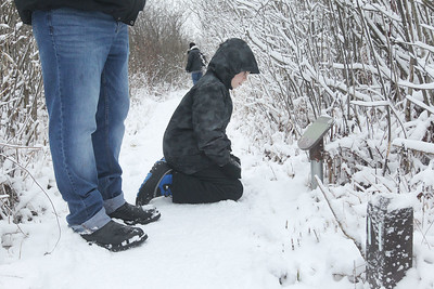 Candace H. Johnson-For Shaw Media Michael Angellotti, of Antioch stops on the boardwalk as his son, Michael, 9, kneels down to read a sign about Early Boggers as they take a Bog Tour during WinterFest at the Volo Bog State Natural Area in Ingleside. (1/12/20)