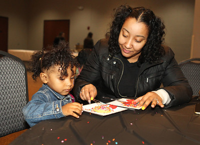 "Candace H. Johnson-For Shaw Media Jaycee Campbell, 2, of Round Lake gets some help from her mother, Juanita, decorating a sugar cookie with icing and sprinkles during Family Fun Friday: Cookie Decorating with Elsa & Olaf at the Round Lake Beach Cultural & Civic Center. The next Family Fun Friday: Creventine Puppet Company's, ""Hands & Strings: A Puppet Variety Show,"" will take place on Friday, Feb. 21st at 1:00 pm. (1/20/20)"