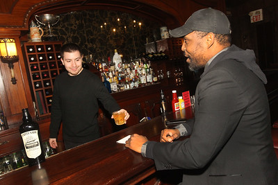 Candace H. Johnson-For Shaw Media Bartender Evan Mikrut, of Mt. Prospect, serves a glass of Scotch whisky to Jay Morris, of Mundelein at the Village Tavern on Old McHenry Road in Long Grove. (1/20/20)