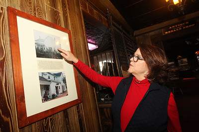 Candace H. Johnson-For Shaw Media Mary Ann Ullrich, co-owner, points to a late 1800's photo taken of the Village Tavern, built in 1847, a she talks about its history on Old McHenry Road in Long Grove. Ullrich owns the full service restaurant with her husband, Chip.(1/20/20)