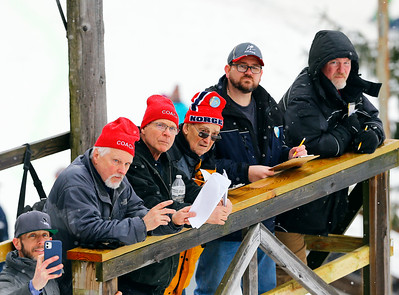 Coaches look on as competitors jump at the Norge Ski Club International Winter Ski Tournament 2020 held on Saturday, January 25, 2020 in Fox River Grove, IL. Saturday's events included junior competitions. The K70 event was canceled due deteriorating weather conditions.