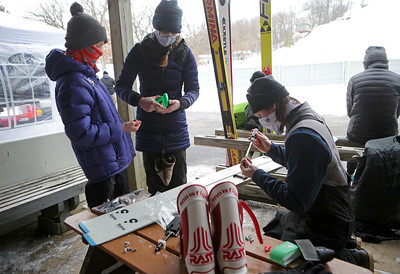 Brian Wallace (right), of St. Paul, Minn., helps Kim (center) and Isaac Larson, 12, mount new bindings on Isaac's skis during the 116th Norge Annual Winter Ski Jump Tournament at the Norge Ski Club in Fox River Grove, Ill., on Saturday, Jan. 30, 2021.