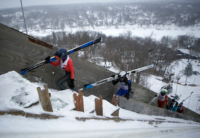 Skiers walk up the steps while competing in the 116th Norge Annual Winter Ski Jump Tournament at the Norge Ski Club in Fox River Grove, Ill., on Sunday, Jan. 31, 2021.