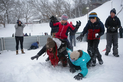 Taryn Sorensen (top), 10, Jack Heaton (top center right), 8, Sierra Kuhlman (bottom right), 10, and Nicole Gutzmer, of Carpentersville, Ill., play in the snow during the 116th Norge Annual Winter Ski Jump Tournament at the Norge Ski Club in Fox River Grove, Ill., on Sunday, Jan. 31, 2021.