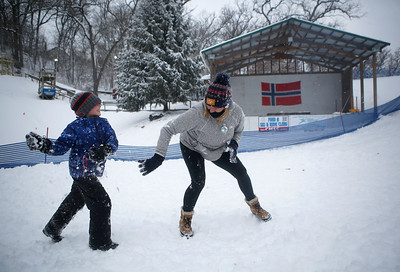 Thayne Sorensen, 7, throws a snowball at Tracey Naumann, of Gilberts, Ill., during the 116th Norge Annual Winter Ski Jump Tournament at the Norge Ski Club in Fox River Grove, Ill., on Sunday, Jan. 31, 2021.