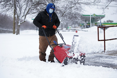 Amador Castro, of 3 AAA Landscaping, uses a snow plow to clear the Cary-Grove Area Chamber of Commerce parking lot in Cary, Ill., on Sunday, Jan. 31, 2021.