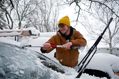 Zeke Hillers cleans snow off his car in Cary, Ill., on Sunday, Jan. 31, 2021.