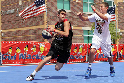 Mike Greene - mgreene@shawmedia.com Street King's Zack Knoblach (left), of Marengo, drives by Midwest All-Star's Tyler Sulaver, 13 of Sycamore, during the 2nd annual Gus Macker 3-on-3 Basketball Tournament at Marengo Community High School Sunday, July 1, 2012 in Marengo.