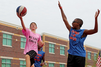 Mike Greene - mgreene@shawmedia.com We Love Chuck's Scott Slocum (left), 12 of Channahon, goes for a layup against Destined to be Drafted's Leroy Patterson Jr., 12 of Chicago, during the 2nd annual Gus Macker 3-on-3 Basketball Tournament at Marengo Community High School Sunday, July 1, 2012 in Marengo.