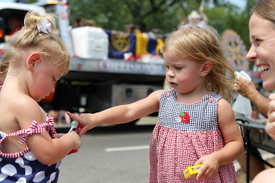 Mike Greene - mgreene@shawmedia.com Haley Schlegel (right), 2 of Pennsylvania, shares candy with Leiah Hjerpe, 2 of Crystal Lake, during the Annual Independence Day Parade Sunday, July 1, 2012 in Crystal Lake. Over 100 different groups participated in the parade from City Hall to the Lakeside Festival.