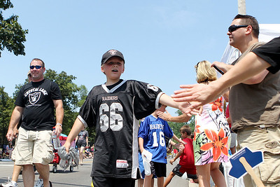 Mike Greene - mgreene@shawmedia.com Crystal Lake Raiders member Alex Millar, 9 of Crystal Lake, gives high-fives to the crowd during the Annual Independence Day Parade Sunday, July 1, 2012 in Crystal Lake. Over 100 different groups participated in the parade from City Hall to the Lakeside Festival.