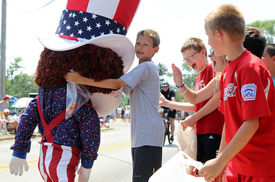 Mike Greene - mgreene@shawmedia.com Kevin Winslow, 13 of Lakewood, hugs a member of Funny Little People during the Annual Independence Day Parade Sunday, July 1, 2012 in Crystal Lake. Over 100 different groups participated in the parade from City Hall to the Lakeside Festival.