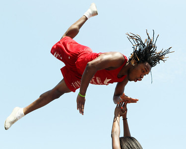 Mike Greene - mgreene@shawmedia.com A member of the Jesse White Tumblers high-fives a teammate while flying through the air during the Annual Independence Day Parade Sunday, July 1, 2012 in Crystal Lake. Over 100 different groups participated in the parade from City Hall to the Lakeside Festival.