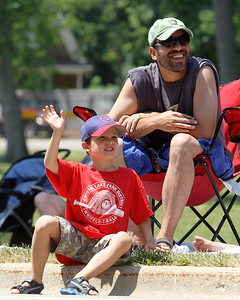 Mike Greene - mgreene@shawmedia.com Miles Davidson, 5 of Crystal Lake, waves at parade participants as his dad Sam watches on during the Annual Independence Day Parade Sunday, July 1, 2012 in Crystal Lake. Over 100 different groups participated in the parade from City Hall to the Lakeside Festival.