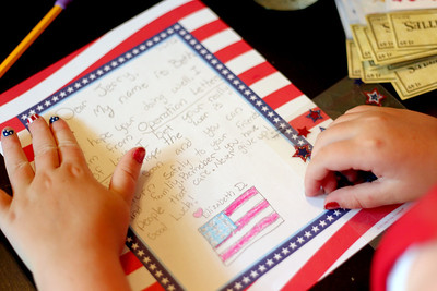 Sarah Nader - snader@shawmedia.com Beth Douglass, 10, of Cary, writes a letter to an active service member overseas For Operation Letters of Love while at her home in Cary on Friday, July 6, 2012.