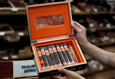 Sarah Nader - snader@shawmedia.com Ken Patel, owner of Kenny the King of Tobacco hold a box of Rocky Patel cigars in his shop in Lakemoor on Tuesday, July 10, 2012.