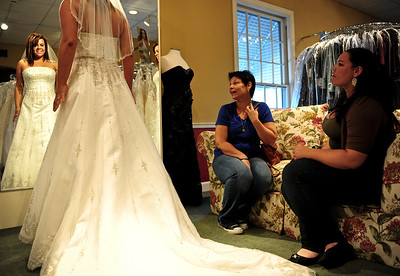 Josh Peckler - Jpeckler@shawmedia.com Malissa Pagan of Chicago (left) looks at herself in a mirror while her mother Maria (center) and sister Melanie look on at Kathryn's Bridal in McHenry Wednesday, July 11, 2012. Pagan was trying on dresses as part of the Brides Across America program that gives brides of military members free wedding dresses.