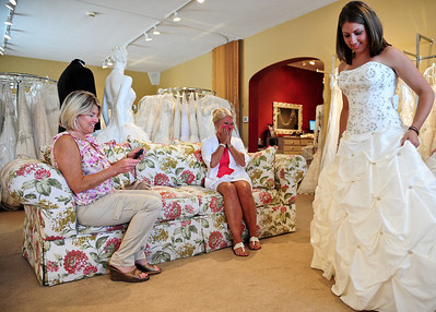 Josh Peckler - Jpeckler@shawmedia.com Darcy Krygsheld of Crete (center) reacts with Julie Smit of Munster, Ind. (left) to seeing her daughter Lindsey Krygsheld in a wedding dress for the first time at Kathryn's Bridal in McHenry Wednesday, July 11, 2012. Krygsheld was trying on dresses as part of the Brides Across America program that gives brides of military members free wedding dresses. Krygsheld's future husband is currently serving in Alaska with the Army. For more photos please go to NWHERALD.COM for a photo gallery.