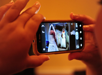 Josh Peckler - Jpeckler@shawmedia.com Malissa Pagan of Chicago (left) looks at herself in a mirror while her  sister Melanie takes a picture with her cell phone at Kathryn's Bridal in McHenry Wednesday, July 11, 2012. Pagan was trying on dresses as part of the Brides Across America program that gives brides of military members free wedding dresses.