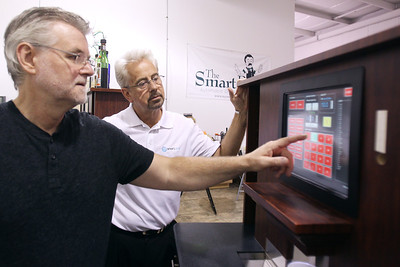 Mike Greene - mgreene@shawmedia.com Smart Bar engineer Fred Knecht (center) watches as Tim Knecht, Director of Engineering, runs diagnostic tests on a new unit Friday, July 13, 2012 at Smart Bar's offices in Crystal Lake. Smart Bar is a robot bartender that was recently implemented in stadiums and casinos and is preparing for a much larger launch later this year.