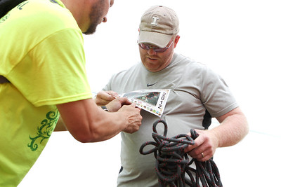 "Mike Greene - mgreene@shawmedia.com Russ Mocklinghoff gets his race badge punched after completing the knot portion of the Rundezvous Race Saturday, July 14, 2012 at Lippold Park in Crystal Lake. The event, billed as a ""frontier survival race,"" took participants on a 5-6 mile race with 14 events including archery, hatchet throwing, logging and more."