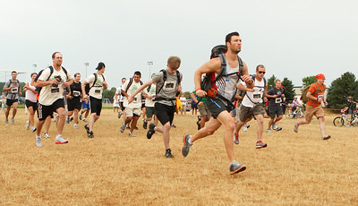 "Mike Greene - mgreene@shawmedia.com Participants take off at the start of the Rundezvous Race Saturday, July 14, 2012 at Lippold Park in Crystal Lake. The event, billed as a ""frontier survival race,"" took participants on a 5-6 mile race with 14 events including archery, hatchet throwing, logging and more."