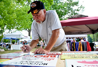 Josh Peckler - Jpeckler@shawmedia.com Jeff Schnell of Cary puts prices tags on homemade signs as he participates in a art fair along the Fox River in Fox River Grove Sunday, July 15, 2012.
